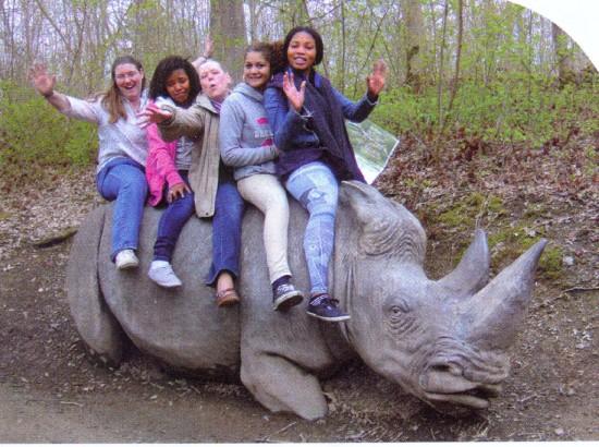 Girls on a stone white rhinoceros